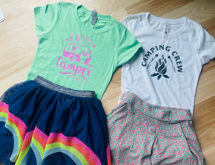Picture of two outfits laid neatly on a wooden floor. The outfit on the left is a mint green tee with an image of a vintage camper with the words 'Happy Camper' and 'Gigi's Wish  2021' on it. The skirt is dark colored with a sequined rainbow on it. The outfit on the right has a white tee with a black image of a camp fire and two marshmallow roasting sticks over it. The words 'Camping Crew' are written in an arch above it. The skirt below it has tiny flowers covering it.