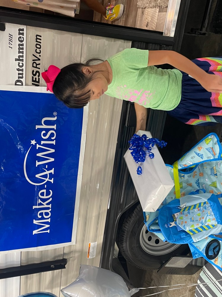 """Image of Gigi, a small Asian girl, standing in front of a small travel trailer with a rectangular blue sign hanging from it. The sign says """"Make A Wish."""" She is holding a present wrapped in white paper with a blue bow on it. She is holding a small blue star shaped balloon. In front of her is a small camping chair and backpack."""
