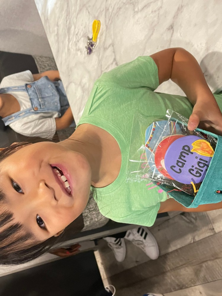 Image of Gigi, a small Asian girl, holding a box of custom cookies. The visible cookie is frosted purple with black letters on it that say 'Camp Gigi.' Gigi is grinning broadly. Her sister Tess, also a small Asian girl, is sitting behind her smiling at the camera.