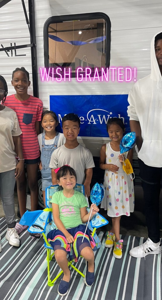 Image of Gigi, a small Asian girl, sitting in front of her travel trailer in her camping chair. She is smiling broadly and holding a blue star balloon. Her siblings Ally, Fox, Tess, Bo, Cate, and Jax are standing behind her smiling as well. The words 'Wish Granted' have been added to the picture in pink text just above the children's heads.