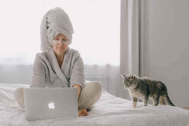 woman wearing a robe using a laptop