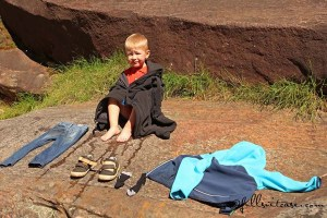 young child traveling in Australia gets wet in natural pools