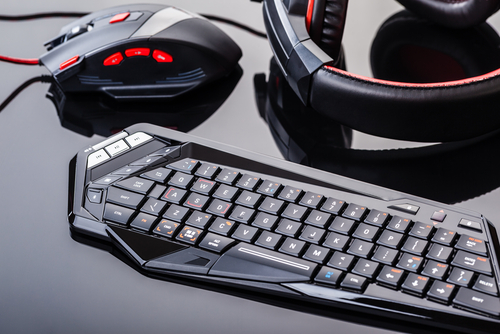 Red and black gaming keyboard, mouse and headset sitting on top of each other on a desk