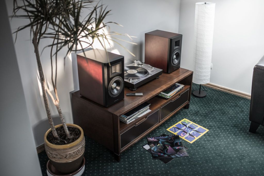 Edifier A300 Bookshelf speakers on a wooden unit divided by a record player placed in between them