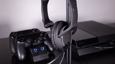 Nighthawk Chat Headset on a stand next to a PS4 and controllers