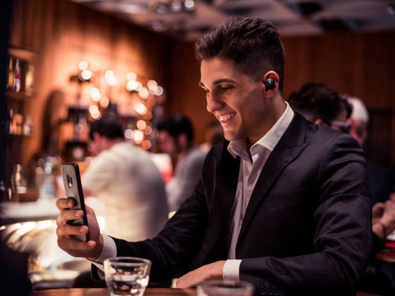A man sitting in a bar making a phone call using the Edifier TWS5 earbuds