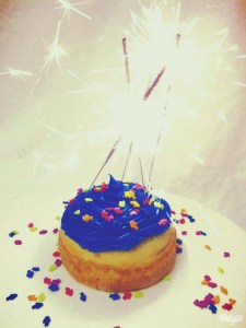 cupcake with blue frosting and multi-colored sprinkles with lit sparklers on top