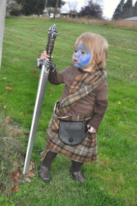 toddler boy in William Wallace Halloween costume from Braveheart, holding a plastic great sword with blue facepaint