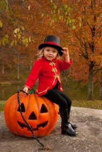 toddler girl in a red lion tamer Halloween costume holding a whip, sitting on an ornamental jack-o-lantern
