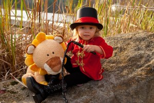 toddler girl in a red lion tamer Halloween costume holding a whip and a stuffed animal lion