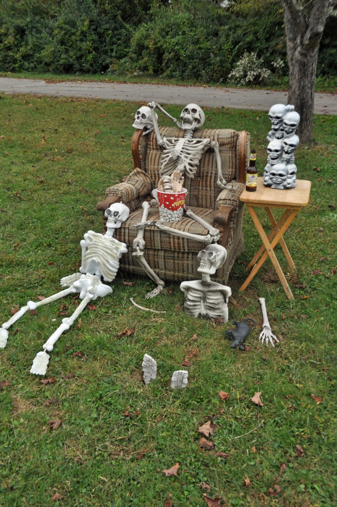 Skeletons arranged in and around an armchair with a popcorn bucket