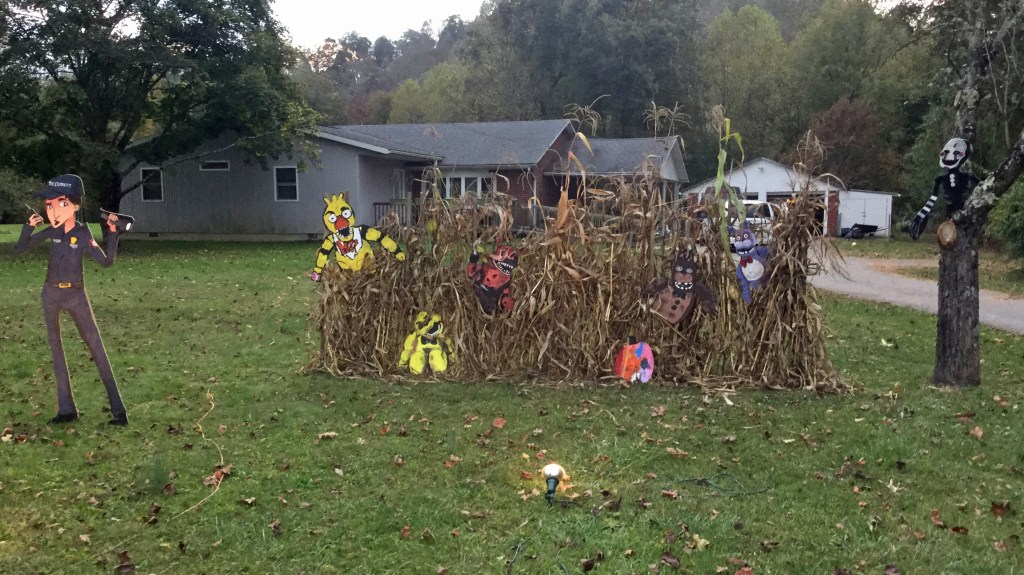 Five Nights At Freddy's Halloween yard display featuring the security guard with Chica, Golden Freddy, Foxy, Real Freddy, and Bonnie popping out of cornstalks behind him and the Puppet Master in the tree.