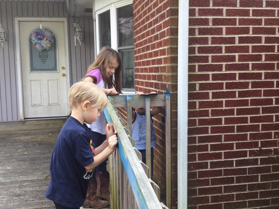 My kids learning to clean blue spray paint off the deck railing with sandpaper