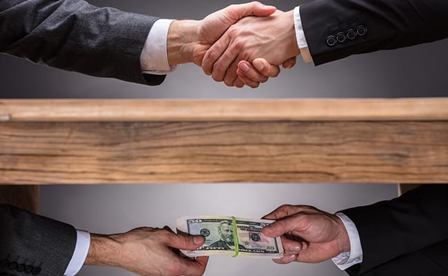 Two people shaking hands also exchanging money under a table