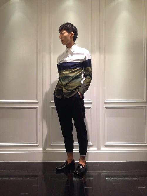 パネルボーダーシャツに黒スラックスを着こなす男性