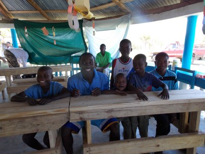 Some of the Haitian students and orphans trying out and enjoying their new table benches