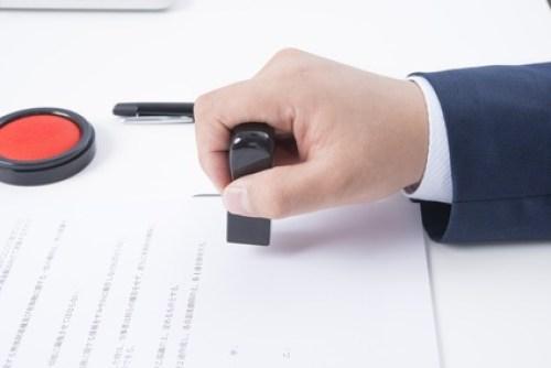 契約書に捺印するビジネスマンの手元