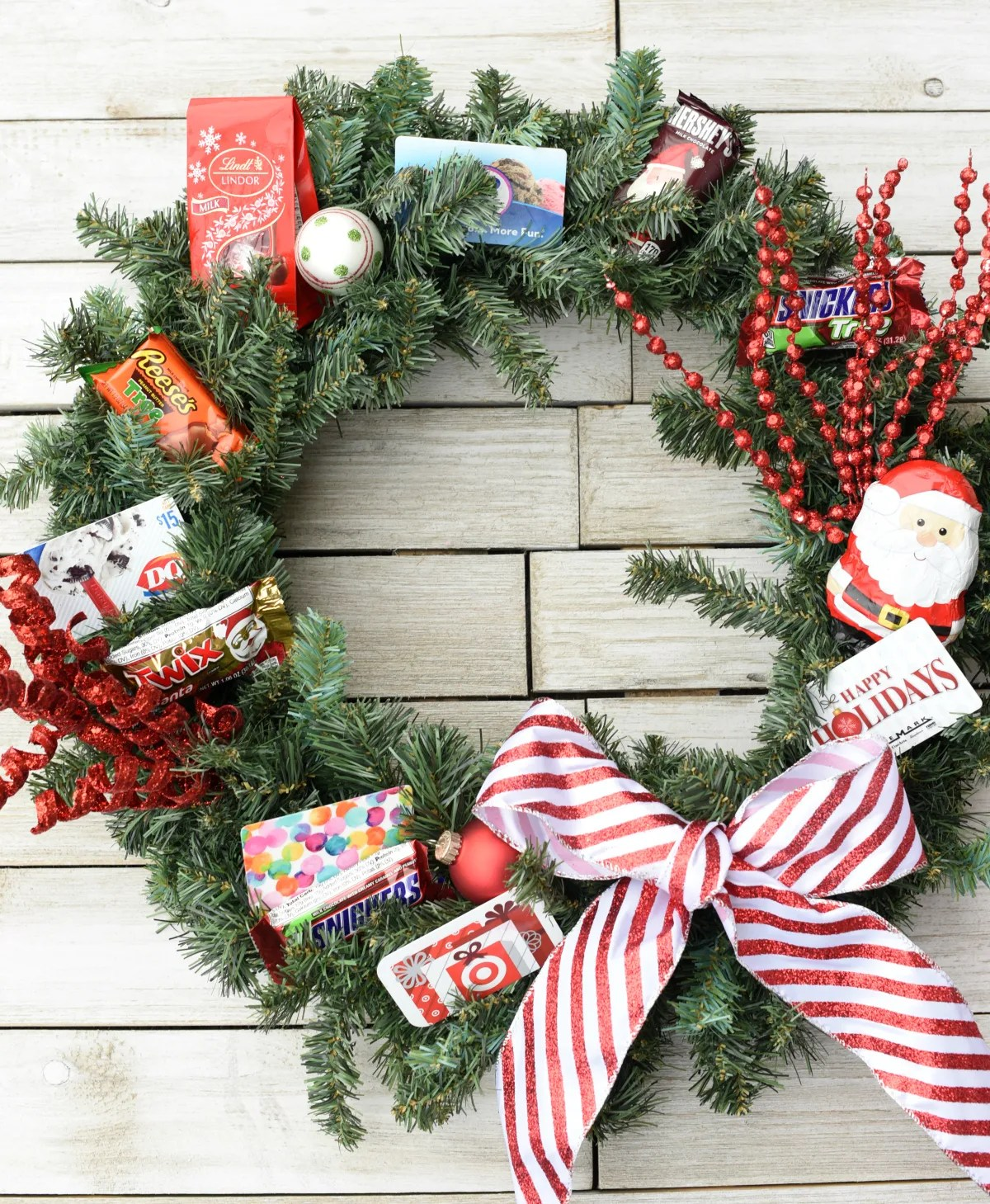 Creative Christmas Gifts-This gift card wreath makes a fun gift to give someone this holiday season! Add gift cards, candy and decorations for a fun, unique and creative Christmas gift idea. #christmasgifts #christmasgiftideas #christmaswreath