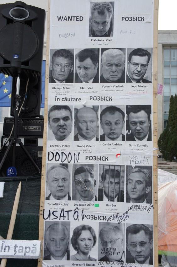 Um placar junto ao edifício do governo mostra fotos de ministros e deputados que se julga implicados no escândalo