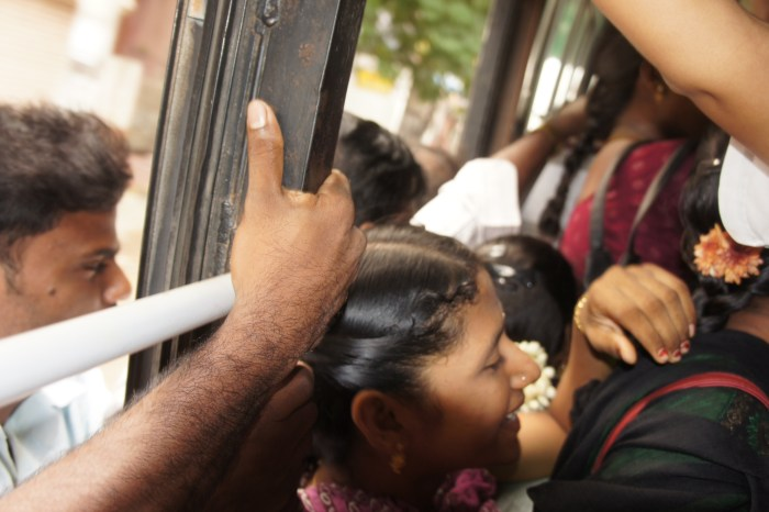 Autocarro pejado de gente... Há pessoas que prosseguem viagem penduradas do lado de fora