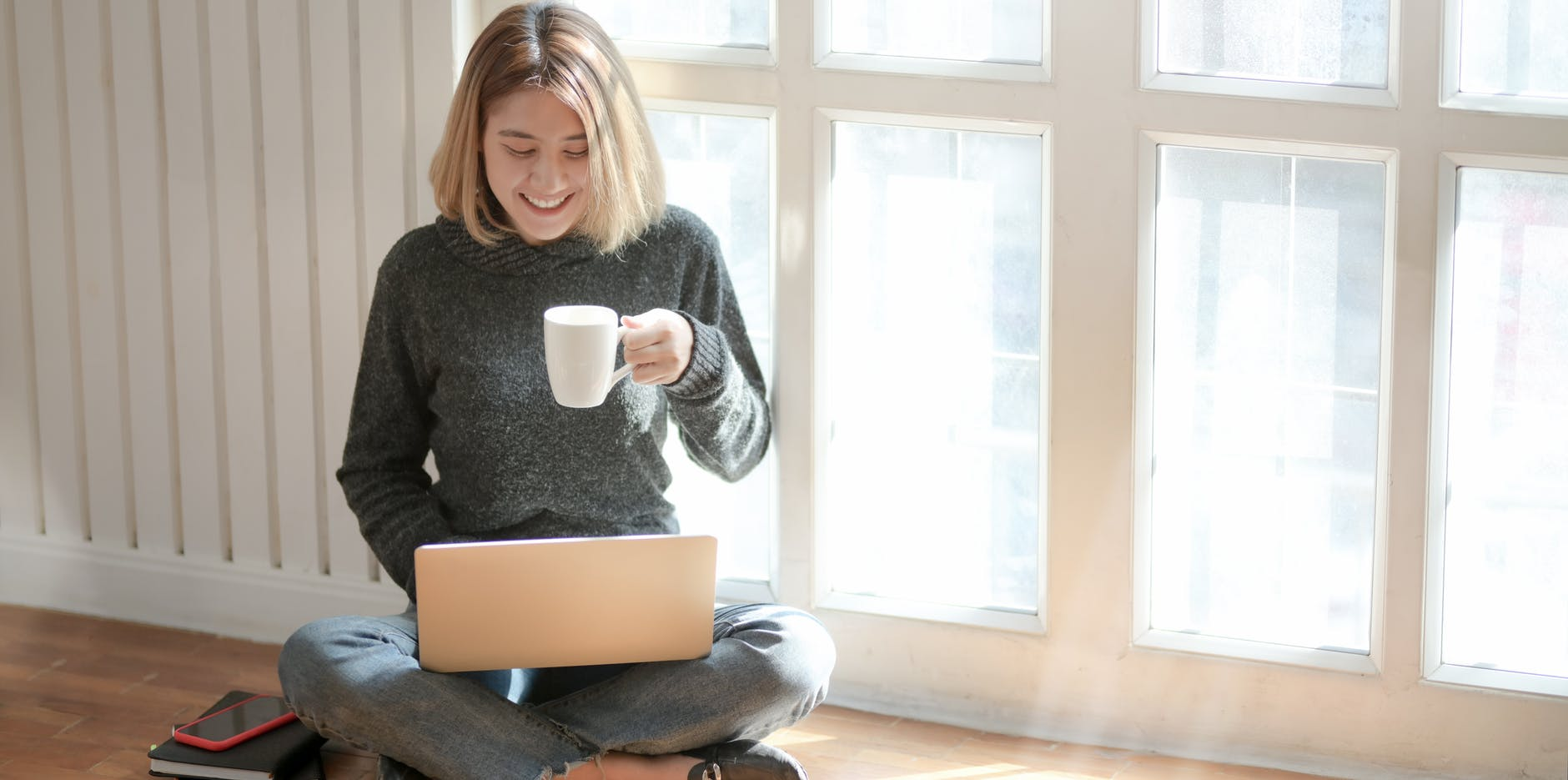 Mujer en su casa, frente al ordenador y con una taza de café