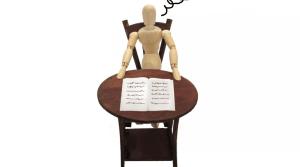 Un muñeco de madera sentado en una mesa miniatura con un documento, sale un humo de su cabeza