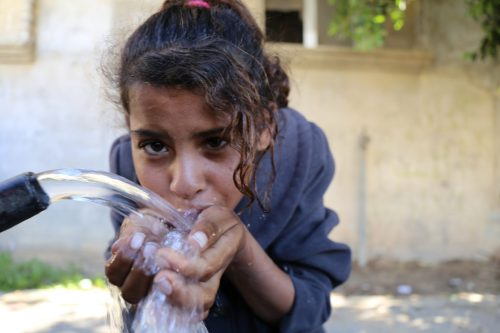 Palestinian girl drinks clean water