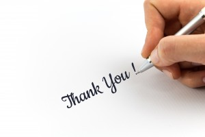 "Hand writing ""Thank You!"" on white sheet of paper."