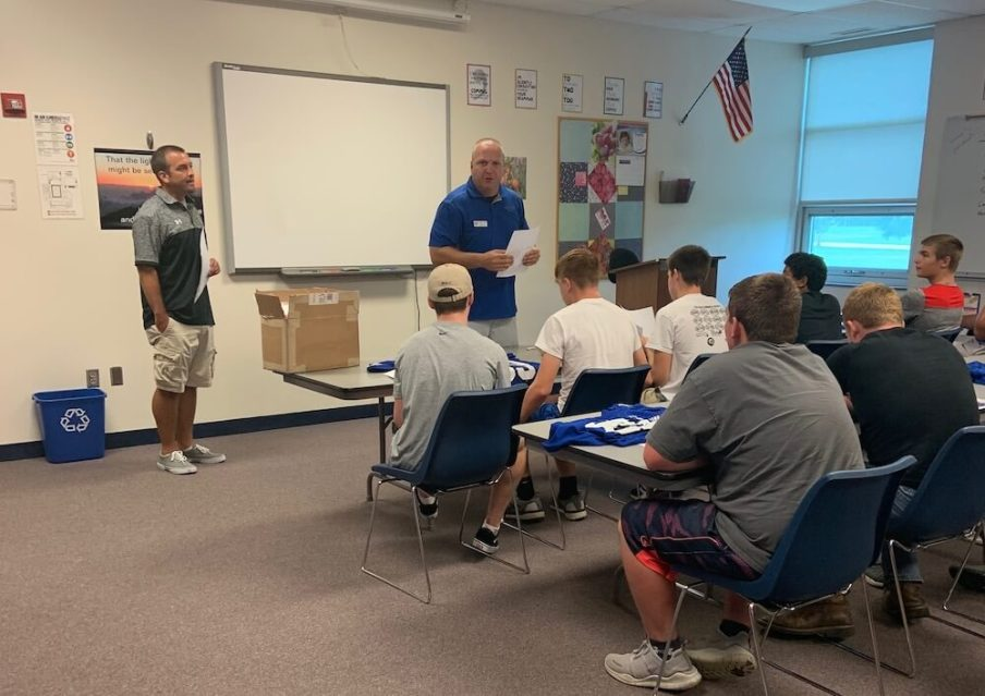Coach and Fund U Coach talk to the football team about fundraising
