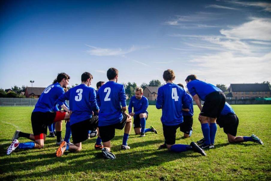 a soccer team in blue uniforms takes a knee to huddle before a game.