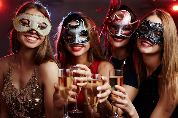 Four girls in masquerade masks with drinks for the New Year