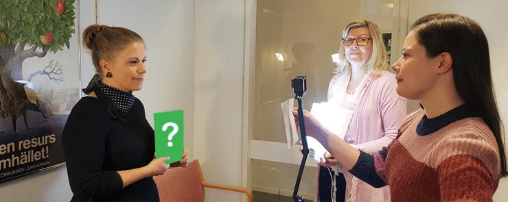 Karin står framför en kamera och håller i en mystisk låda med ett frågetecken på. Lena står intill och håller i en lampa för att rikta ljuset mot Karin. Annelie står mitt emot Karin, bakom kameran.