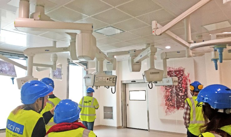 Väl upplyst operationssal, med skärmar och annan utrustning monterad på armar i taket.