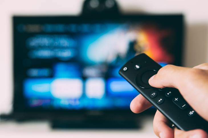 Using a remote control to select Netflix show. Unsplash