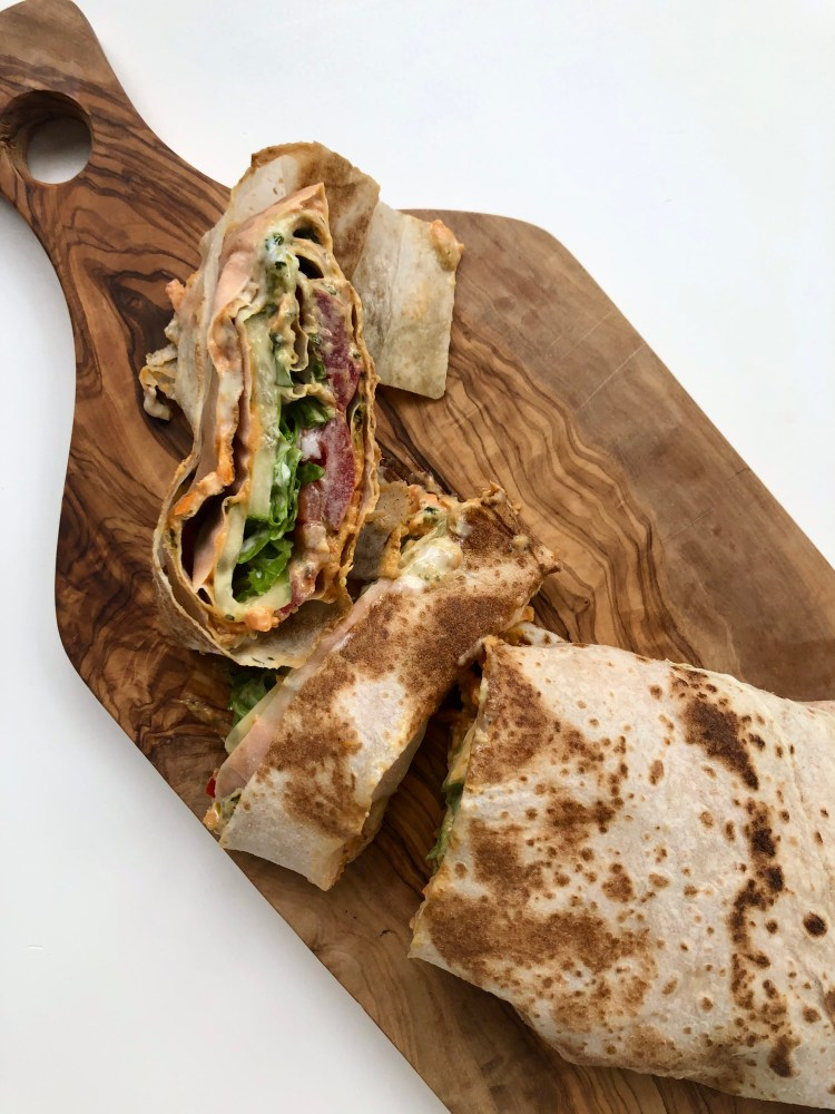 markouk sandwich wrap with vegetables and hummus on a cutting board
