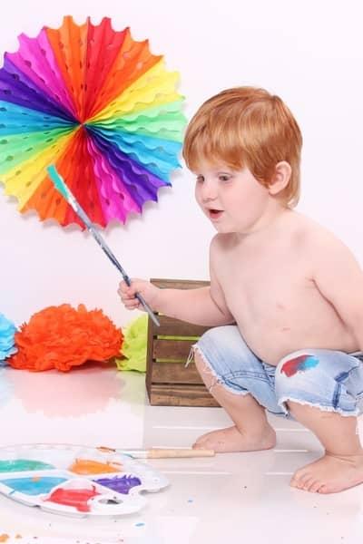 toddler holding paintbrush