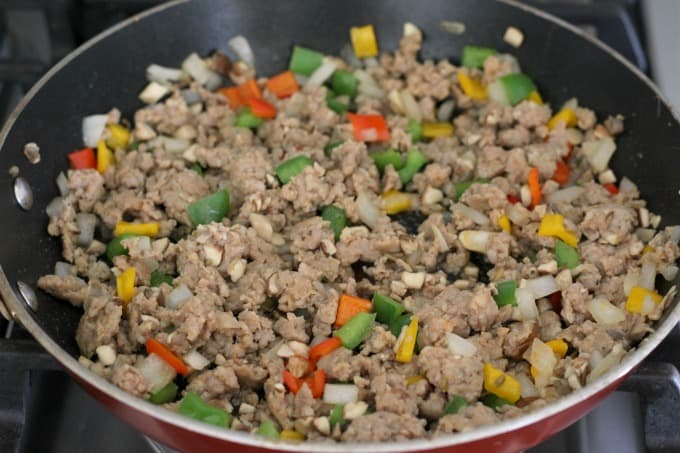 Cook the mushrooms, sausage, peppers and onion until sausage is cooked through.