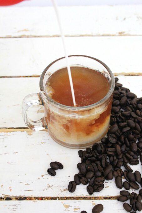 Adding cream to gingerbread coffee
