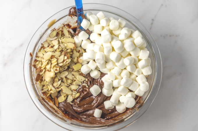 Marshmallows and almonds in melted chocolate