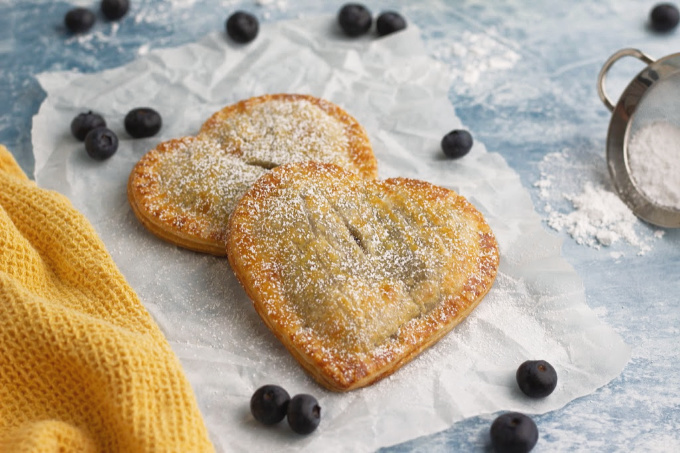 Blueberry hand pies on blue background