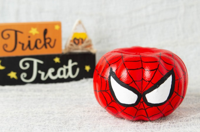 Spiderman pumpkin with a trick or treat sign