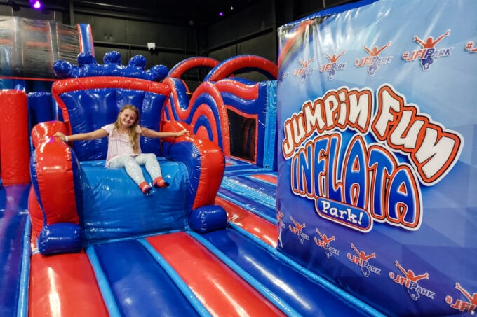 Girl sitting in inflatable chair at Jumpin' Fun Inflata Park