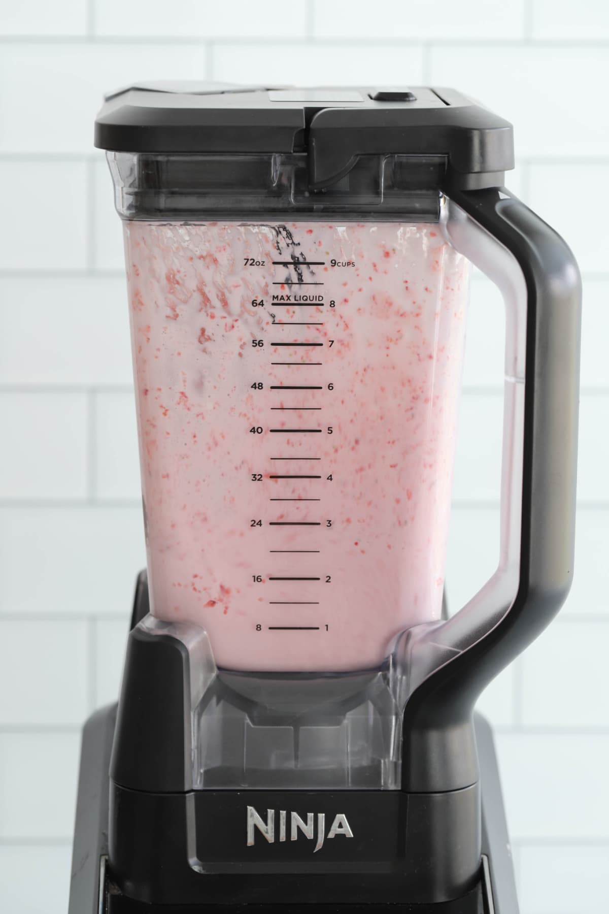 Blending all the strawberry milkshake ingredients
