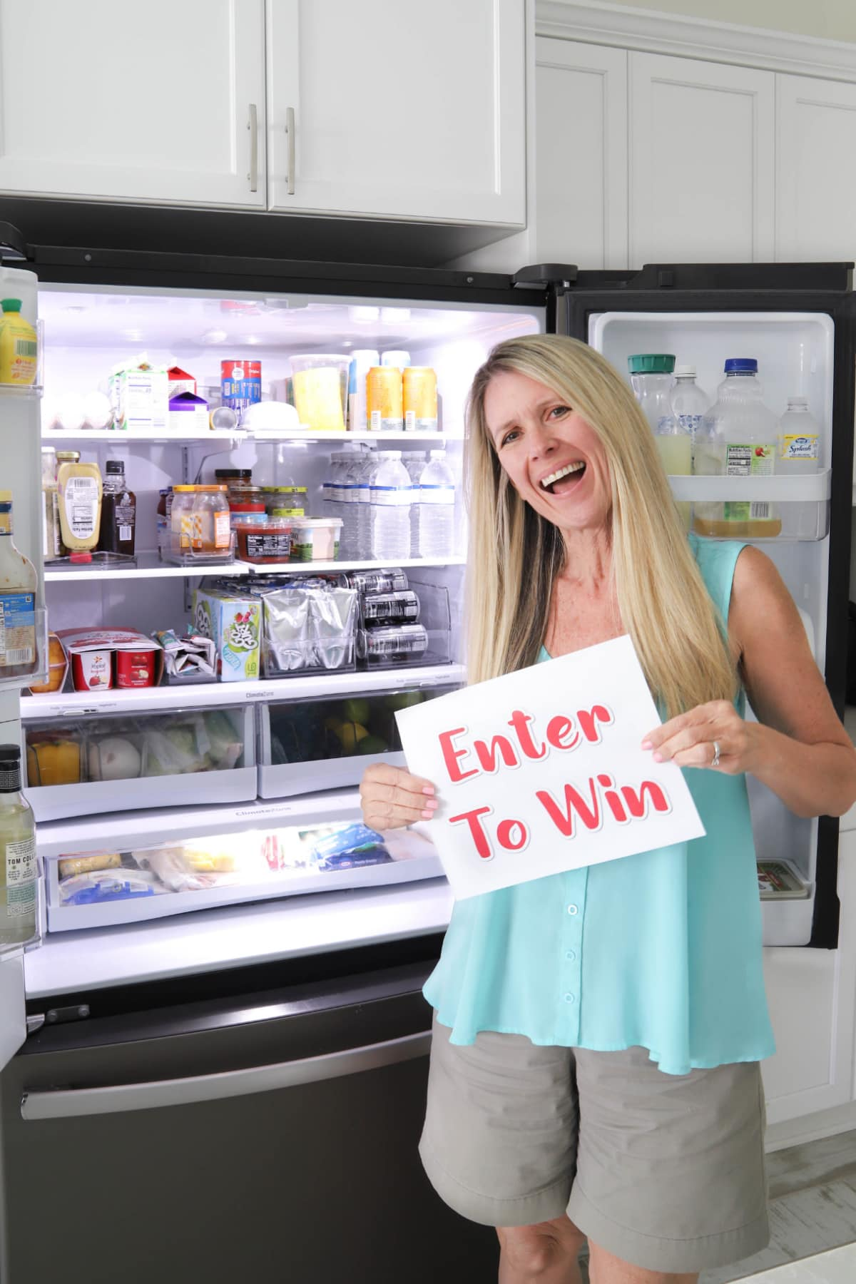 Woman holding enter to win sign in front of fridge