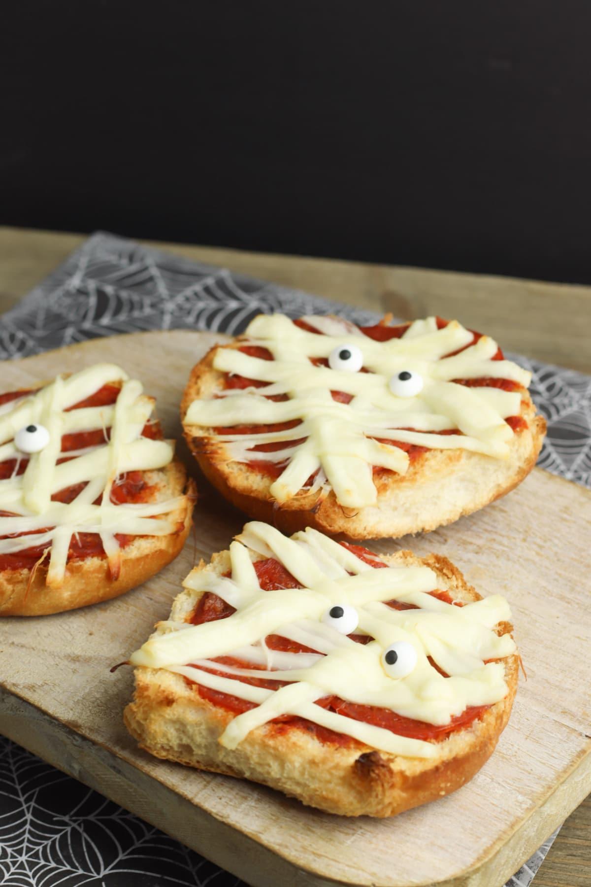 Three mummy pizzas on cutting board