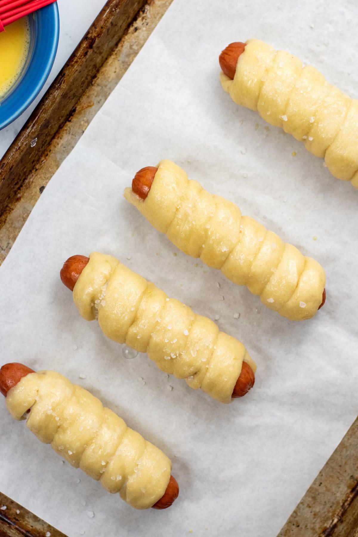Salted pretzel dogs on a baking sheet