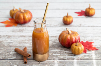 Pumpkin juice with pumpkins and leaves around it