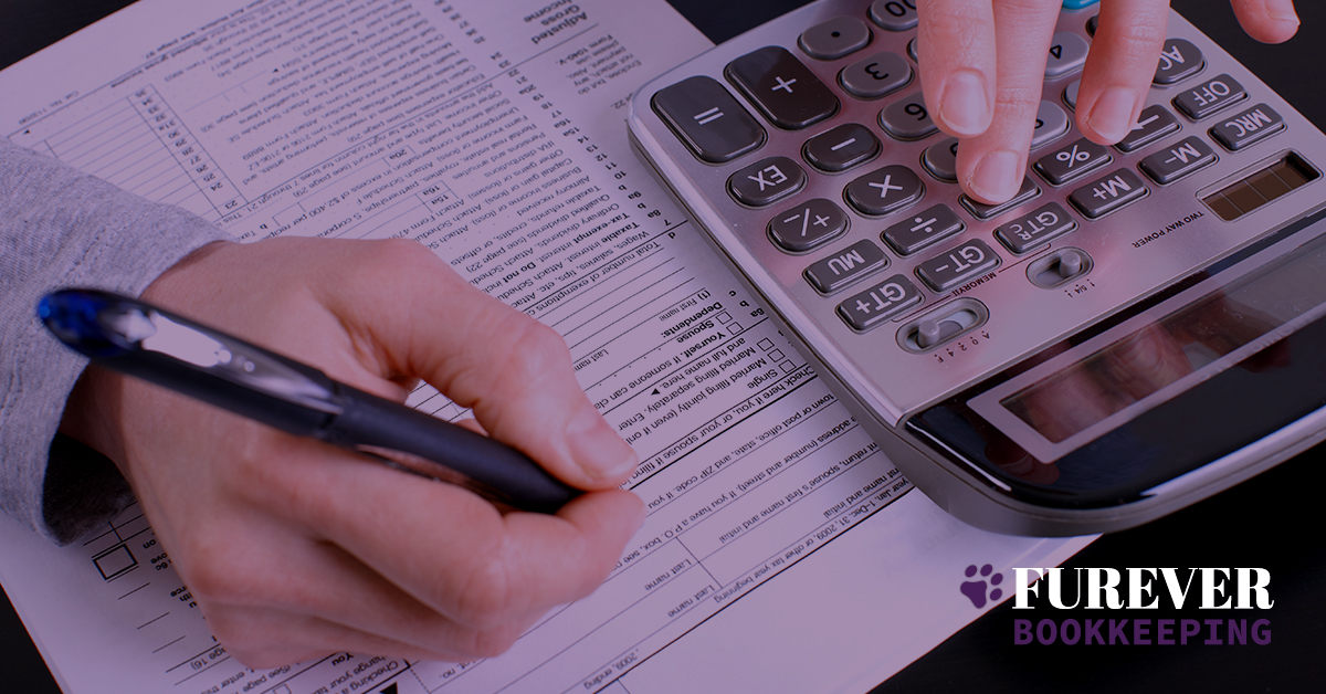 female using calculator and writing results on tax paperwork Furever Bookkeeping