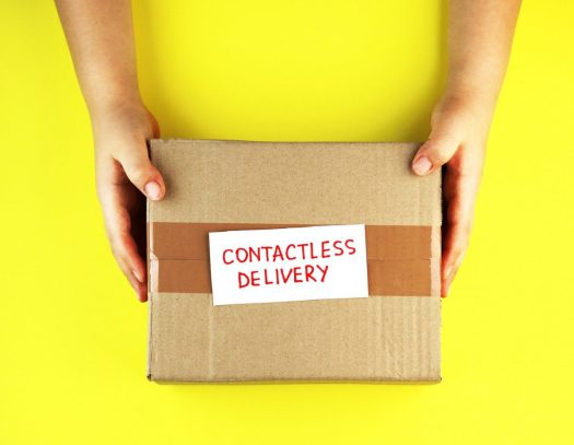 a pair of hands holding a box that says 'contactless delivery' on a yellow background