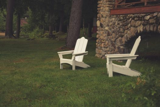 two Adirondack type white lawn chairs sit on a grassy lawn beside an old stone house